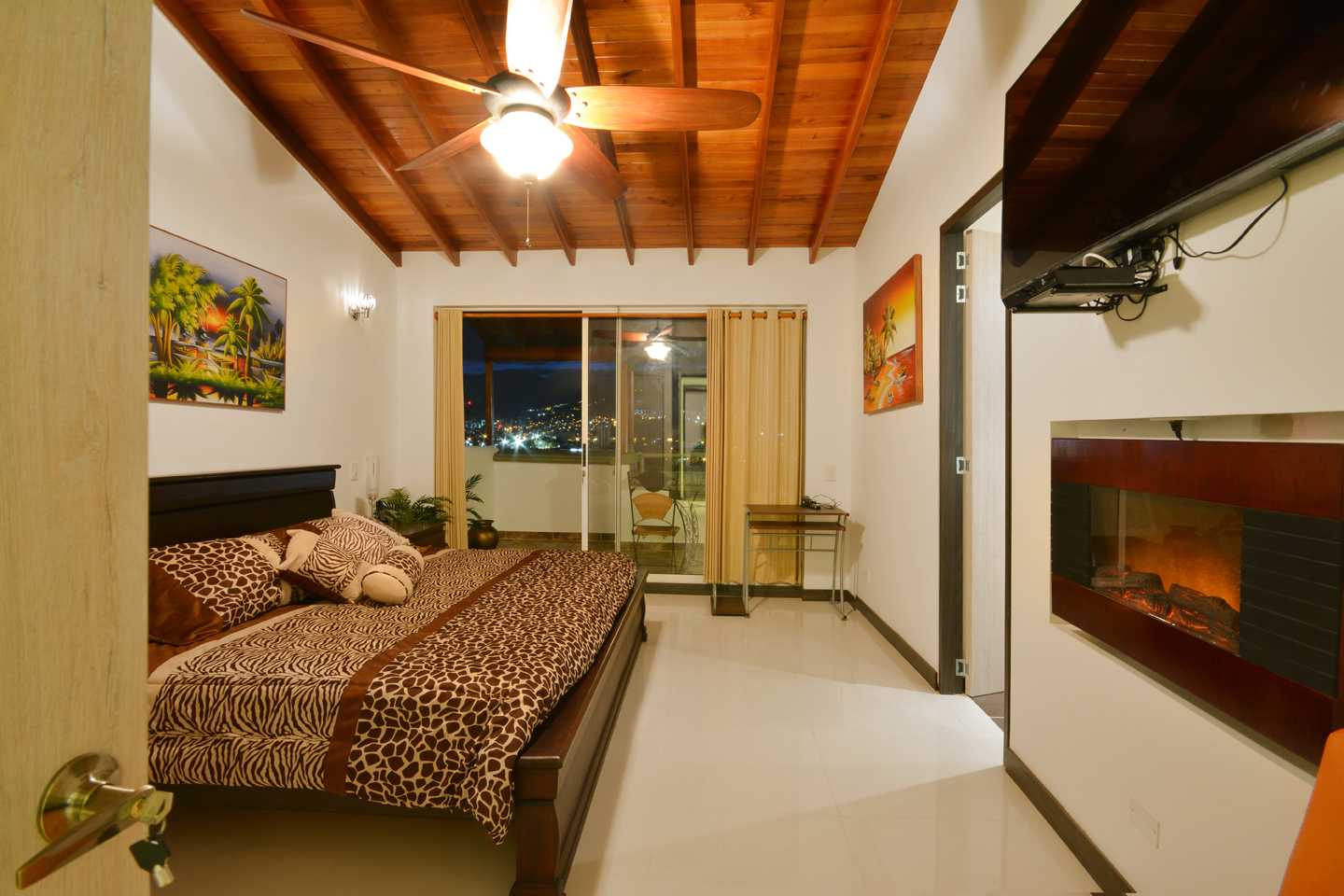 Bedroom 1 with fireplace, outdoor deck, flat screen TV, high ceilings and ceiling fan in Astorga duplex