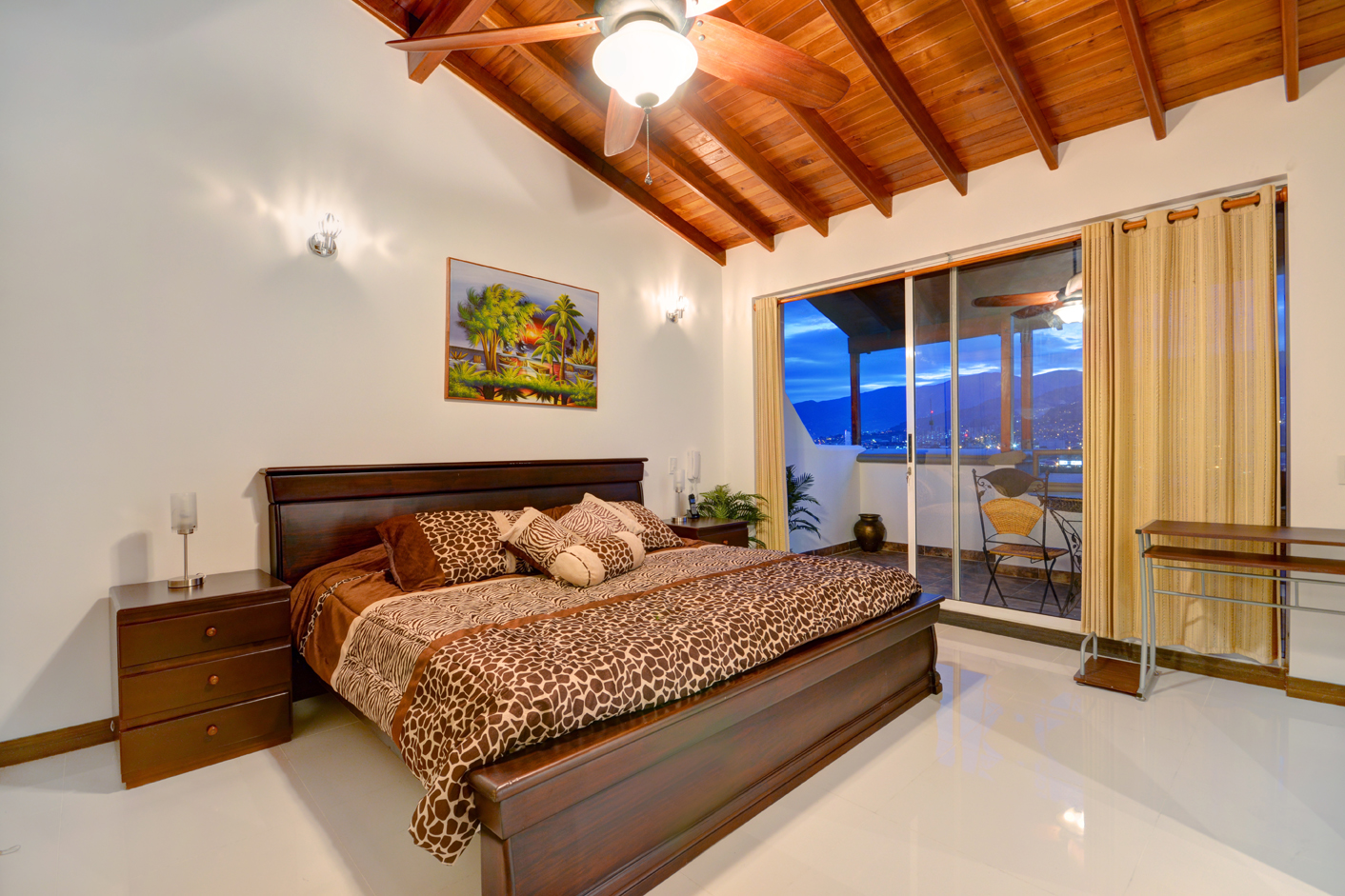 Bedroom 1 with adjacent covered deck, high ceilings and ceiling fan.