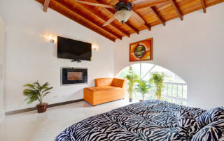 Clean, contemporary bedroom 2 with wide screen TV, fireplace, high ceiling and ceiling fan.